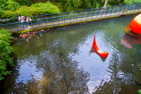 HAKONE, JAPAN - JULY 02, 2017: Unidentified people looking at red abstract installation in the pond of Hakone open air museum Editorial