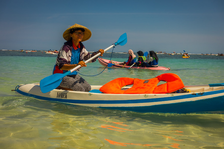 BALI, INDONESIA - MARCH 11, 2017: Unidentified woman enjoying the beautiful sunny day over a kayak in the beach of Pantai pandawa, in Bali island, Indonesia Editorial