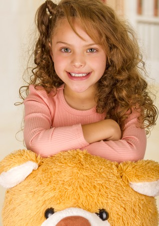A portrait of a young pretty girl smiling and posing over her teddy bear head in a doctor office background