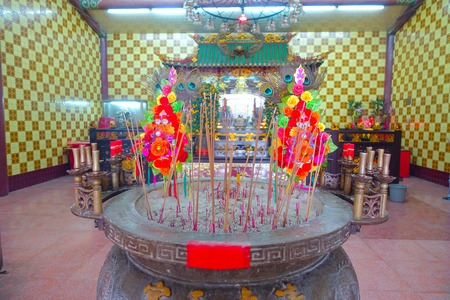 HONG KONG, CHINA - JANUARY 26, 2017: Tsz wan temple, with a hell representation, with an inciense over a table with some plastic roses in ash, in Hong Kong, China. Editorial