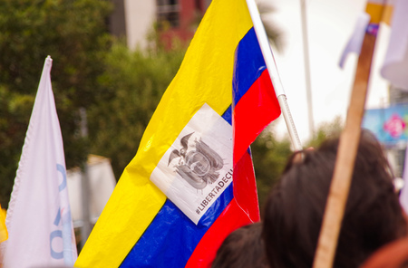 Quito, Ecuador - April 7, 2016: Closeup of an Ecuadorian flag holded by a person, claiming for liberty and supporting the presidential candidate Guillermo Lasso, and journalists during anti government protests in Shyris Avenue