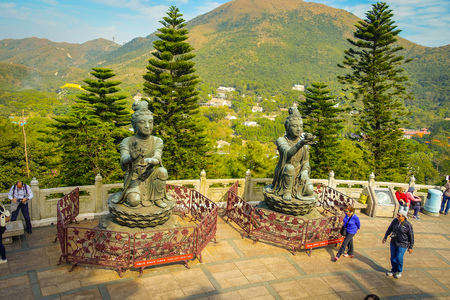 palate: HONG KONG, CHINA - JANUARY 26, 2017: Unidentified people walking around of a beautiful statues, located in the entrance of the Tian Tin monastery, in a sunny day in Lantau Island, Hong Kong.