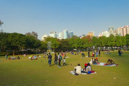 HONG KONG, CHINA - JANUARY 26, 2017: Crowd of people, resting on the grass, in victoria park in hong kong. Victoria park is the biggest flower market during the chinese new year. Stok Fotoğraf - 82783462