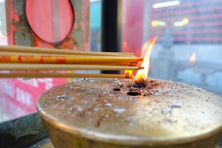 Close up of an incense burning up over a bronze tray with fire in the middle at Wong Tai Sin Temple, Hong Kong, China.