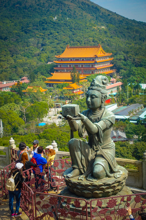 palate: HONG KONG, CHINA - JANUARY 26, 2017: Unidentified people walking around of a beautiful statue, located in the entrance of the Tian Tin monastery, in a sunny day in Lantau Island, Hong Kong Editorial
