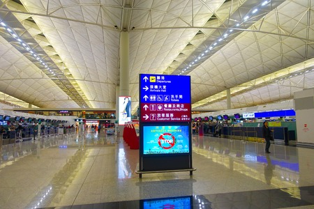 ceiling: HONG KONG, CHINA - JANUARY 26, 2017: Unidentified people walking near of informative sign inside of the airport of Hong Kong Editorial