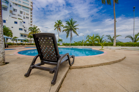 inground: Esmeraldas, Ecuador - March 16, 2016: Beautiful swimming pool with circle form, with a rattan chair in the border in a luxury hotel at Same, Ecuador