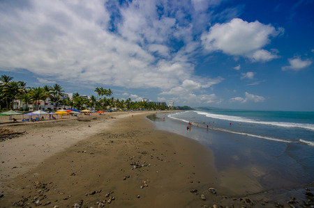 SAME, ECUADOR - MAY 06 2016: Beautiful view of the beach with sand, and builsings behind in a beautiful day in with sunny weather in a blue sky in Same, Ecuador