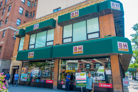 NEW YORK, USA - JUNE 22, 2017: Unidentified people walking at the exterior of the famous photo and video B and H store, in the beautiful city of New York with skyscrapers and gorgeous buildings in New York City, fish eye effect