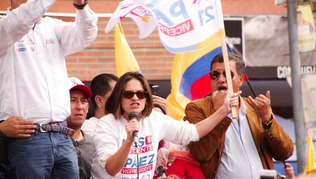 Quito, Ecuador - April 7, 2016: Unidentified people with ecuadorian and white flags talking in microphone and supporting the presidential candidate Guillermo Lasso, and journalists during anti government protests in Shyris Avenue Editorial