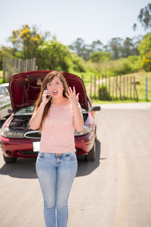Desseperated woman calling to report car damaged on country Road in a beautiful sunny day