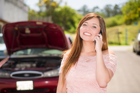 Smiling young woman calling to report car damaged on country Road in a beautiful sunny day Stock Photo