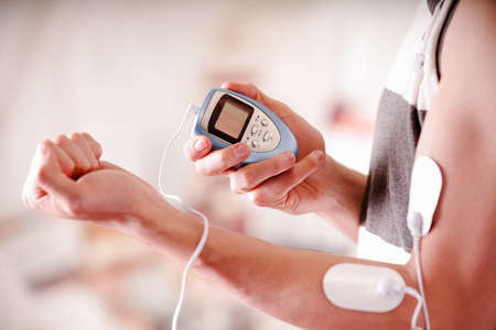 Close-up of a man holding an electrode machine in his hand and with electrostimulator electrodes in the arm of a fitness young man in a blurred background