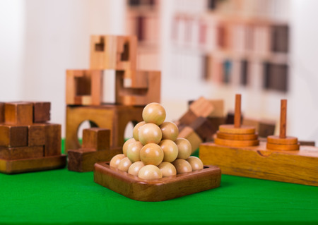 Assorted wooden brain teaser or wooden puzzles on green table in a blurred background.