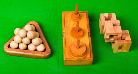 Assorted wooden brain teaser or wooden puzzles on green background.