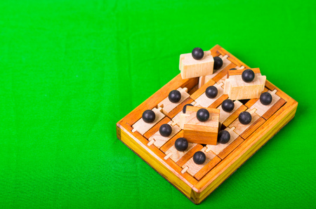 Wooden Brain Teaser or Wooden Puzzles on green background