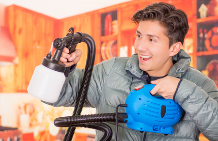 Close up of handsome smiling man holding in his hands the painting spray gun, an wearing a gray jacket in a blurred background Stock Photo