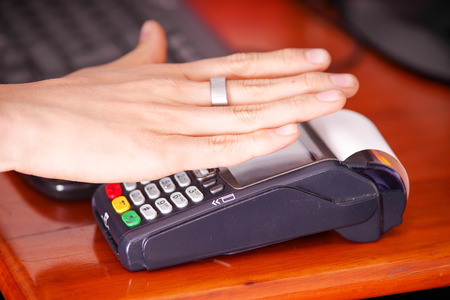 Modern payment with new technology of payments using a smart ring, buy and sell products service on a wooden table Stock Photo