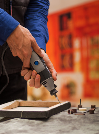 hardworker: Closeup of a hardworker man drilling a wooden frame with his drill, with drilling accessories over a gray table in a blurred background