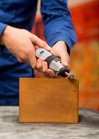 Closeup of a hardworker man wearing a blue t-shirt and using a polisher in a piece of wood, on a gray table in a blurred background