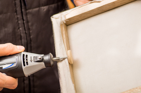 hardworker: Closeup of a hardworker man holding with one hand a frame and using a polisher in a wooden frame with his other hand Stock Photo
