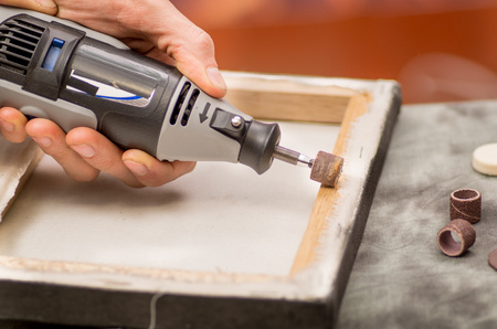 hardworker: Closeup of a hardworker man using a polisher in a wooden frame, on a gray table in a blurred background Stock Photo
