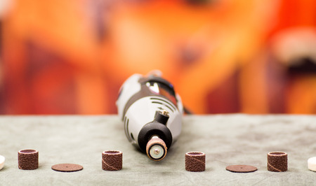 auto repair: Close up of a drill with drilling accessories on gray table in a blurred background Stock Photo