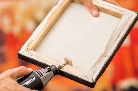 hardworker: Closeup of a hardworker man holding with one hand a frame and using a polisher in a wooden frame with his other hand in a blurred background