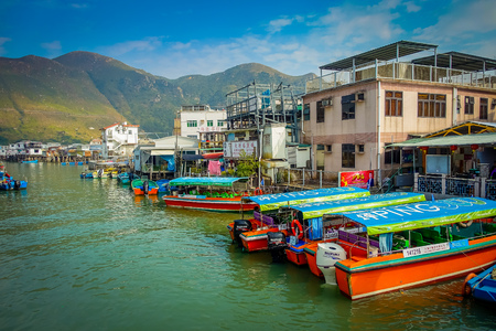 HONG KONG, CHINA - JANUARY 26, 2017: Riverboats in dirty river of old fishermen village Tai O with rustic houses, in a beautiful sunny day in Hong Kong