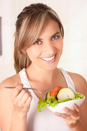 Beautiful young woman wearing a white t-shirt and holding in her hand a healthy salad Stock Photo