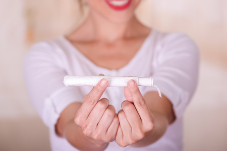 Close up of a young woman pointing in front of her a menstruation cotton tampon and manipulating the tampon, in a blurred background