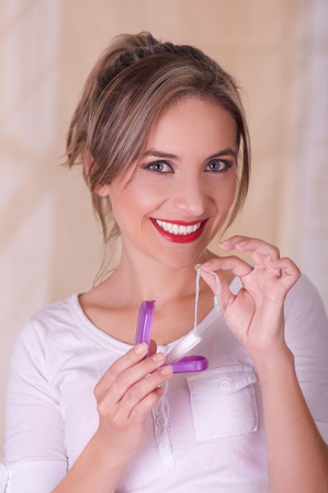 Young beautiful smiling woman holding a menstruation cotton tampon in one hand and with her other hand a plastic purple box Stock Photo