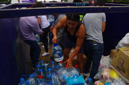 fema: Quito, Ecuador - April,17, 2016: Unidentified people on a car providing water for earthquake survivors in the coast
