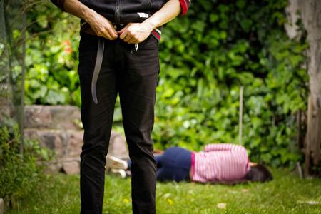 Primo piano di un uomo che si aggiusta i pantaloni dopo un abuso sessuale, con la donna che posa nel terreno dietro lo stupratore. Stupro e concetto di abuso sessuale Archivio Fotografico