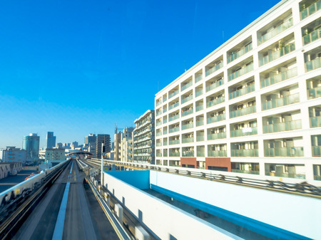 TOKYO, JAPAN JUNE 28 - 2017: Scenery of a train traveling on the elevated rail of Yurikamome Line in Odaiba, Minato, Tokyo, under blue clear sunny sky Editorial