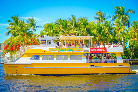 FORT LAUDERDALE, USA - JULY 11, 2017: Colorful yellow water taxi with a gorgeous view of river walk promenade highrise condominium buildings and yachts in Fort Lauderdale, Florida