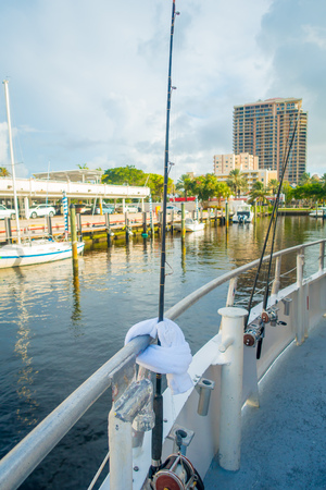 FORT LAUDERDALE, USA - JULY 11, 2017: Three big game fishing rods in a big boats parked in the water in the pier at the Fort Lauderdale International Boat Show Editorial