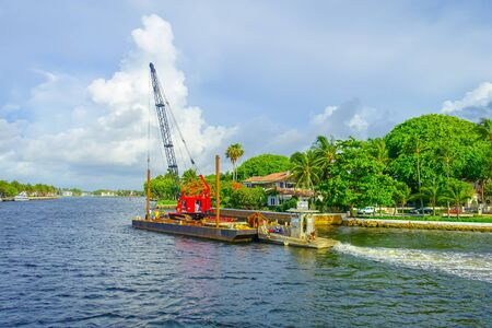 city and county building: FORT LAUDERDALE, USA - JULY 11, 2017: Floating structure with a red machine over it sailing in the riverwalk promenade, highrise condominium buildings behind in Fort Lauderdale, Florida