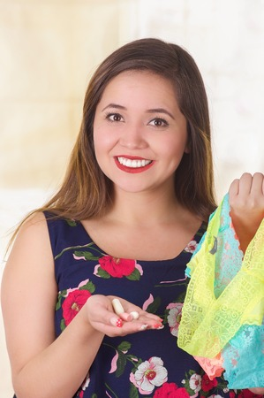Close up of a smiling young woman, holding an assorted colorful underwears and a soft gelatin vaginal tablet or suppository, treatment of diseases of the reproductive organs of women and prevention of womens health
