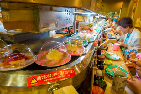 TOKYO, JAPAN -28 JUN 2017: Unidentified people eating an assorted japanesse food over a table, inside of a kaitenzushi conveyor belt sushi restaurant. Consumers pile up colored empty plates when they are finished eating, in Tokyo