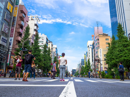 TOKYO, JAPAN -28 JUN 2017: Unidentified people walking and taking pictures in the street in Town of Akihabara, in Tokyo, in a beautiful blue sky Editorial