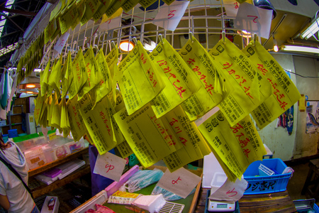 TOKYO, JAPAN JUNE 28 - 2017: Informative yellow signs at the Tsukiji Wholesale Seafood and Fish Market in Tokyo Japan. Tsukiji Market is the biggest wholesale fish and seafood market in the world, Fish eye effect
