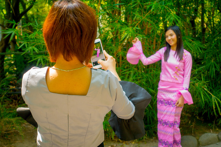 TOKYO, JAPAN JUNE 28 - 2017: Unidentified woman taking pictures to a her friend who is posing to camera wearing a pink dress in Kamakura, Japan