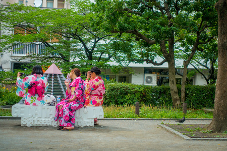 TOKYO, JAPAN JUNE 28 - 2017: Unidentified group of women wearing a kimono dress and taking selfies to theirself, sitting in a white public chair in a park near of the Buddhist Temple Sensoji in Tokyo, Japan. The Sensoji temple in Asakusa area is the oldes