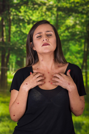 Young woman wearing a black blouse and suffering from itch after mosquito bites, in a blurred green background