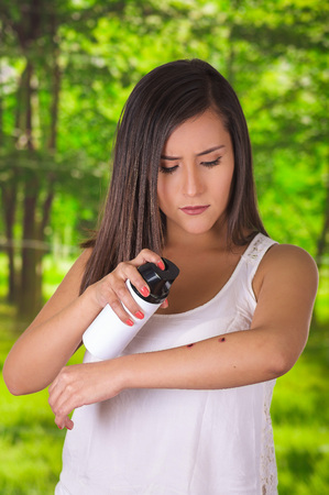 Close up of young woman suffering from itch after mosquito bites, using a spay over the insect bite, allergic skin treatment concept, in a green forest background Stock Photo