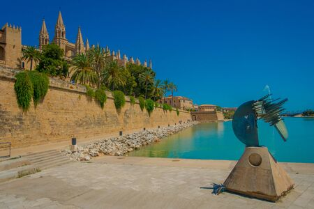 PALMA DE MALLORCA, SPAIN - AUGUST 18 2017: Beautiful view of Cathedral of Santa Maria of Palma La Seu in a gorgeous blue sky, with an artifical pond with a fountain in the middle, in Palma de Mallorca, Spain