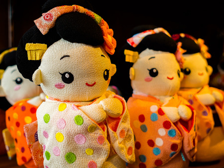 HAKONE, JAPAN - JULY 02, 2017: Japanese traditional japanesse dolls on a blurred background mass-produced products. Selective focus in a store in hanami Kyoto