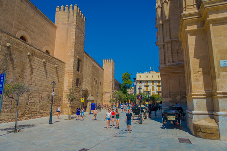 PALMA DE MALLORCA, SPAIN - AUGUST 18 2017: Unidentified people walking near of Cathedral of Santa Maria of Palma La Seu in a gorgeous blue sky, in Palma de Mallorca, Spain