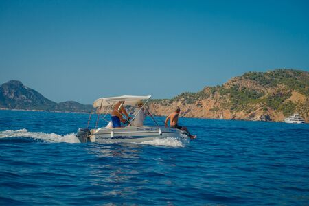 mallorca: PORT D ANDRATX, SPAIN - AUGUST 18 2017: Unidentified family enjoying the view of the blue water and a beautiful blue sky, in Port D Andratx, located in Mallorca balearic islands, Spain